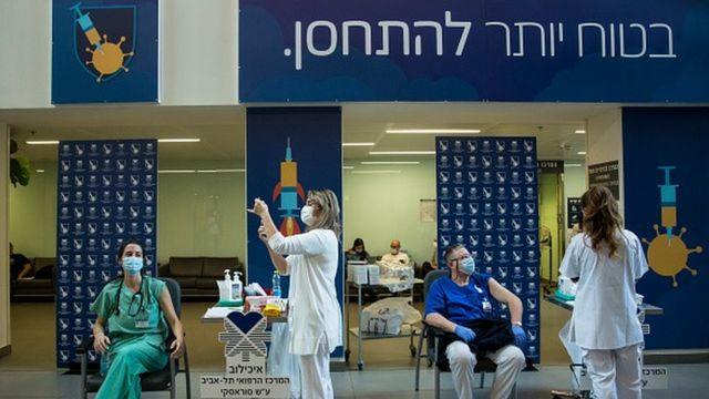 Ponto de vacinação em Israel, em que duas pessoas estão sentadas para receber a vacina contra a covid-19