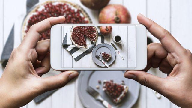 Celular tomando foto de comida.