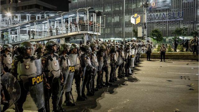 ตำรวจยืนปิดกั้นผู้ประท้วงระหว่างการชุมนุมที่ด้านหน้าหน่วยงานตรวจสอบเลือกตั้ง