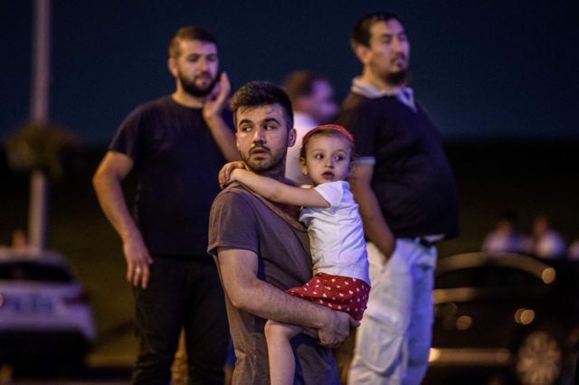Un hombre carga a una niña a las afueras del aeropuerto.