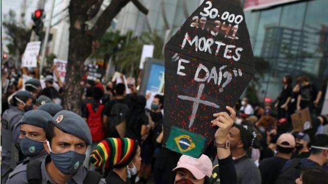 Em protesto, com policiais e manifestantes de máscara, pessoa levanta cartaz em formato de caixão e frase: 30 mil mortes, e daí?