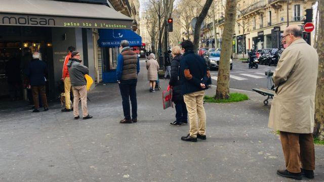 Paris'te baget ekmeği almak için sıraya girenler, aralarına mesafe koymaya dikkat ediyor