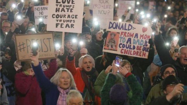 متظاهرون يحملون لافتات