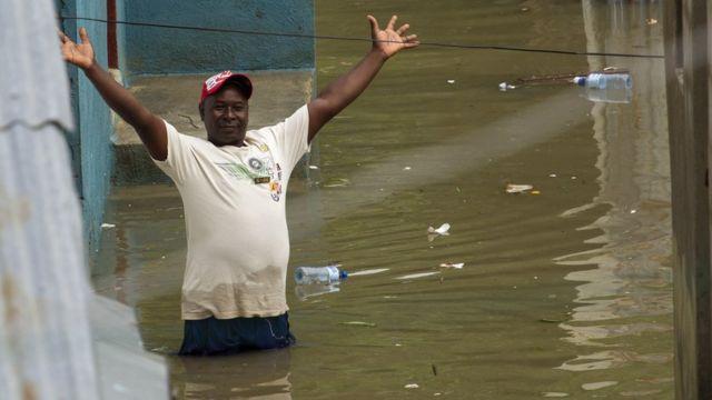 Hombre en una calle inundada en Santo Domingo.