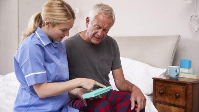 cuidadora ajudando homem idoso