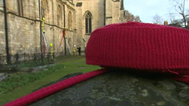 Red scarf being hung on the exterior of a church
