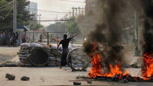 Un manifestante gesticula cerca de una barricada durante una protesta contra el golpe militar en Mandalay, Myanmar, el 22 de marzo de 2021.