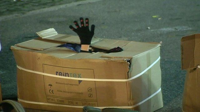 Someone in a cardboard box, with their hand poking out of the top