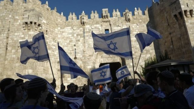 Israeli nationalists wave Israeli flags outside the Damascus Gate of Jerusalem's Old City (15 June 2021)