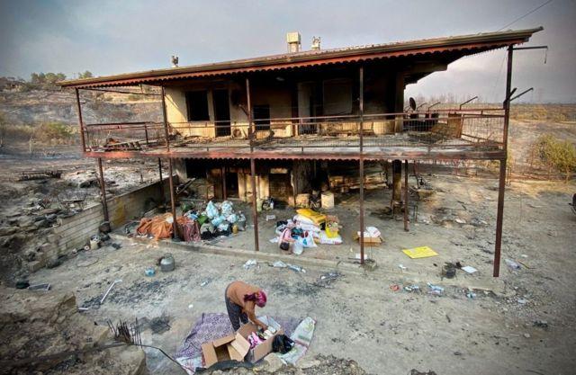 Manavgat'ta bir kadın yanan evinin önünde