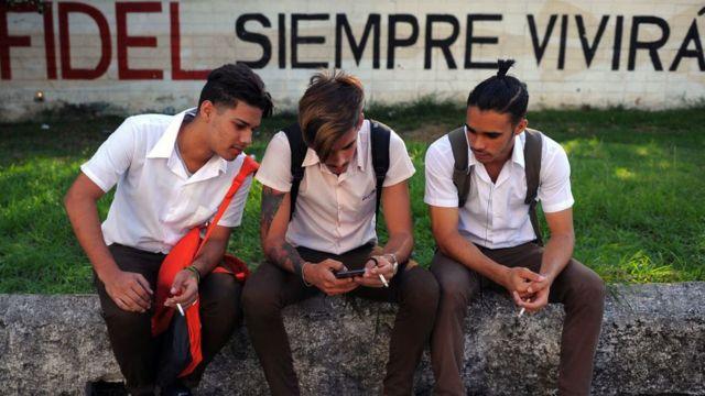 Rapazes usando celular em Cuba