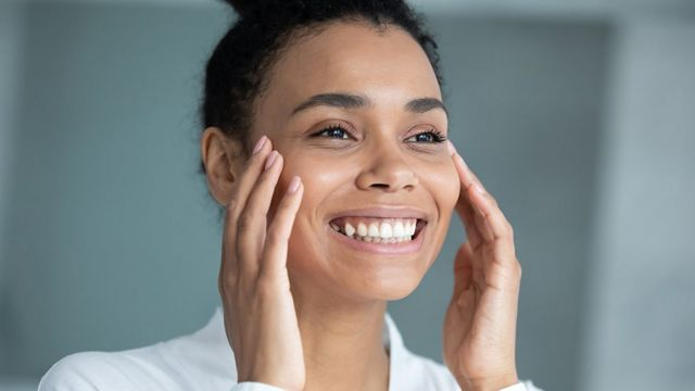 Smiling woman with hands on face