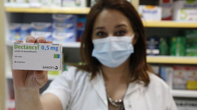 Una boticaria sostiene una caja con el medicamento dexametasona