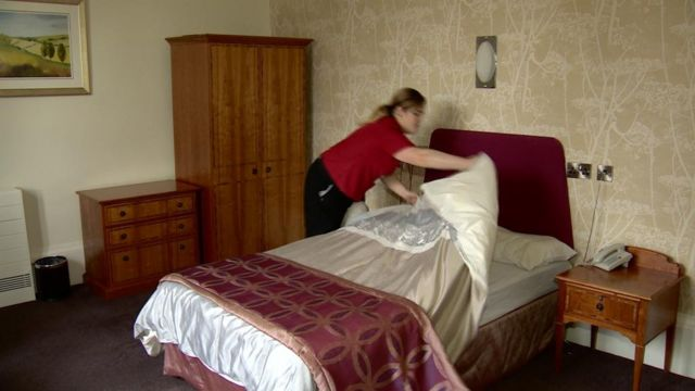 Hospitality worker making bed