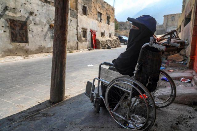 أروى ناجي، بعد إصابتها بجروح خلال قصف التحالف بقيادة السعودية على حيها في 2015 ، تجلس على كرسي متحرك أمام منزل مهجور في حي الجميلية في تعز في 13 فبراير 2021 ، حيث تعيش مع أطفالها الأربعة الصغار.