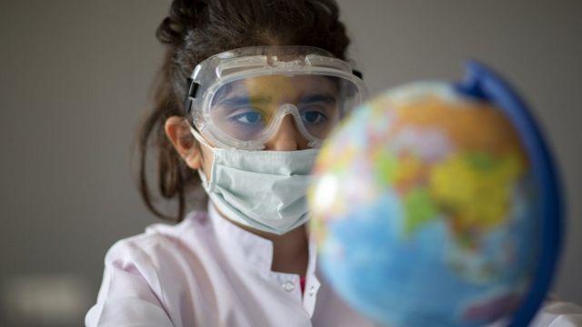 Menina usando máscara e óculos de proteção diante de globo terrestre