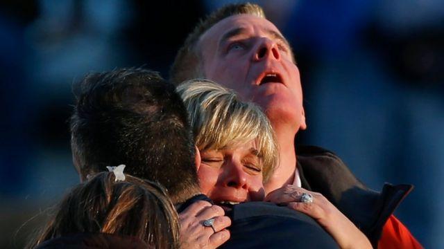 Familiares de las víctimas en la escuela de Sandy Hook se consuelan mutuamente.