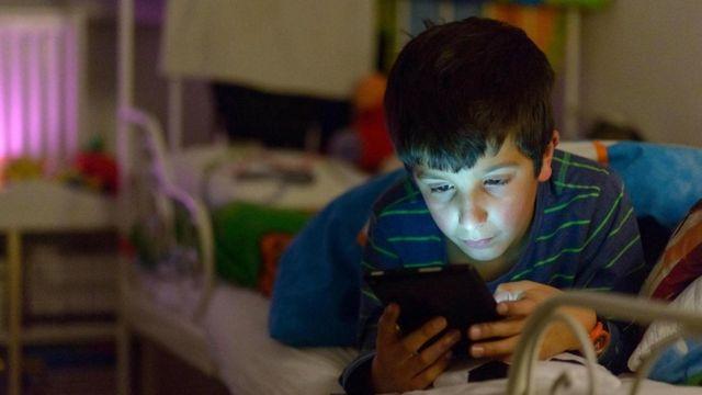 شاب يحمل هاتفه الجوال وينظر إليه وهو في فراشه