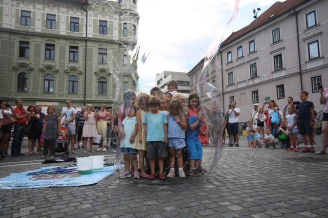 Imagem mostra crianças dentro de uma bolha de sabão observadas por grupo de adultos, em uma praça na Europa