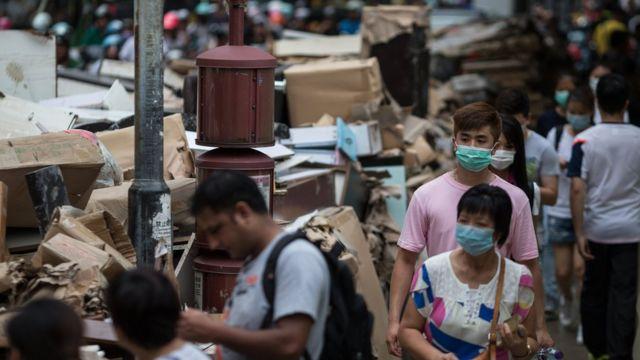 戴着口罩的澳门居民走过堆积如山的灾后垃圾(25/8/2017)