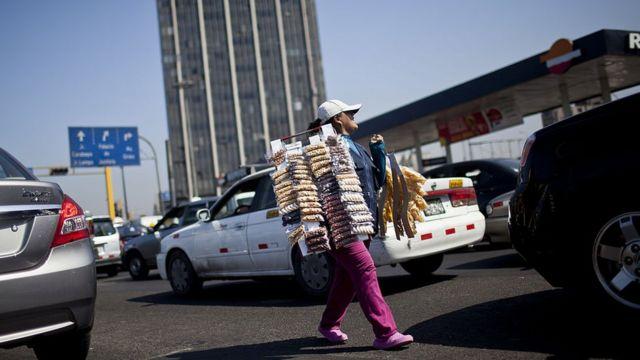 Una mujer vende snacks por las calles de Lima.