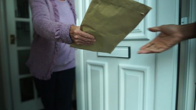 Reconstruction of pensioner handing over package of cash to criminal
