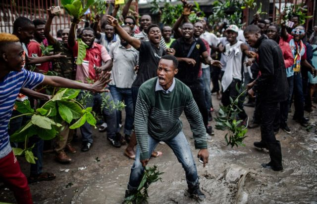 """Protesters waiting to cast their ballot, demonstrate outside the College St Raphael polling station, in Kinshasa, on December 30, 2018 while DRC""""s electoral commission president arrives for the DR Congo's general elections"""