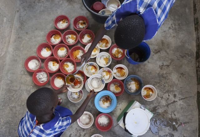 Two children dish out food