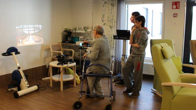 Dois adolescentes ensinam um senhor de idade a jogar um jogo virtual, projetado na parede