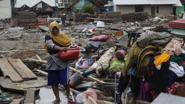 Mulher entre ruínas de área atingida por tsunami na Indonésia
