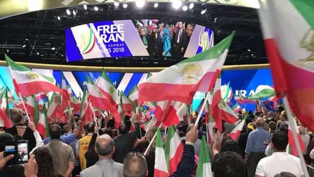 أشخاص يلوحون بالأعلام الإيرانية أثناء التجمع