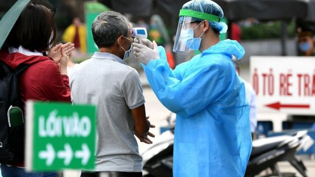 Nhân viên y tế mặc đồ bảo hộ kiểm tra nhiệt độ của người vào bệnh viện Bạch Mai, Hà Nội vào ngày 24 tháng 3 năm 2020