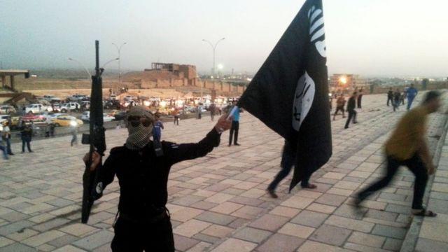 मोसुल में आईएस के झंडे के साथ एक लड़ाका.