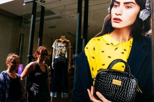 Dos mujeres caminan frente a una tienda en París.