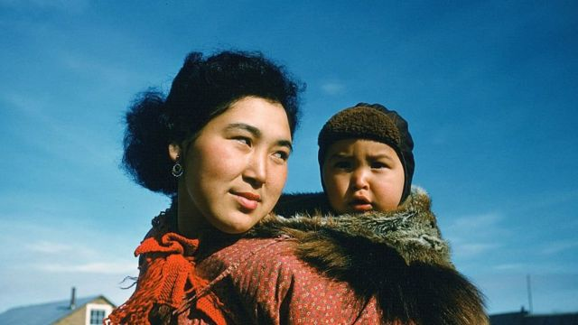 CIRCA 1955: A portrait of an Inuit women and her baby on her back in Unalakleet,Alaska.