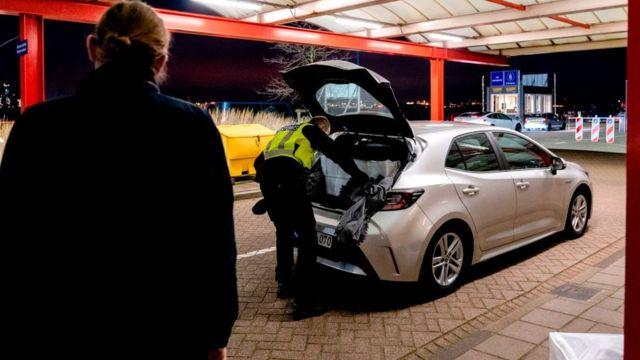 Un agente fronterizo en Hoek van Holland inspecciona el baúl de un auto que viene de Reino Unido