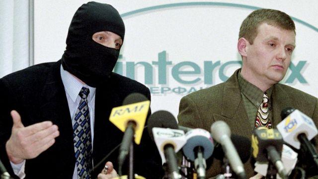 Litvinenko (à direita), com o rosto coberto, fala em uma conferência de imprensa em 1998