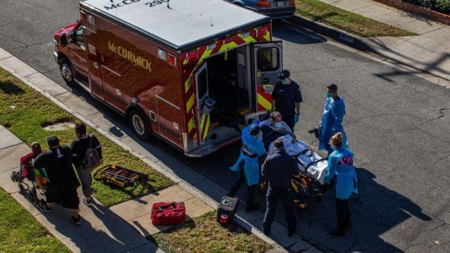 Funcionários de ambulâncias do condado de Los Angeles transportam um paciente suspeito de covid-19 para o hospital