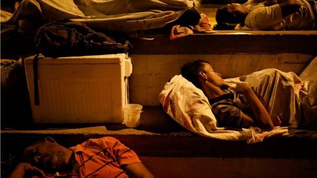 Hombres duermen encima de sábanas en el piso de un centro deportivo.