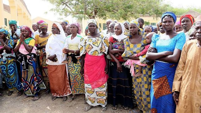 This picture taken on March 5, 2015 the mothers of Chibok Schoolgirls siezed by Boko Haram Islamist fighters on the evening of April 14, 2014, wait the arrival of Minister of Finance Ngozi Okonjo-Iweala to flag off rebuilding of schools burnt by the militants in Chibok, Northeastern Nigeria