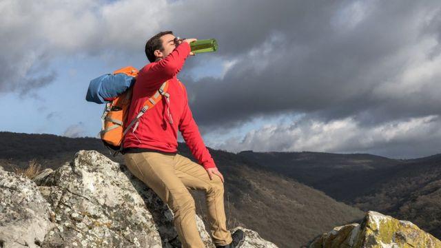 Hombre tomando agua de una botella en una montaña.