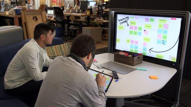 Em escritório, dois homens em frente a tela com lousa virtual