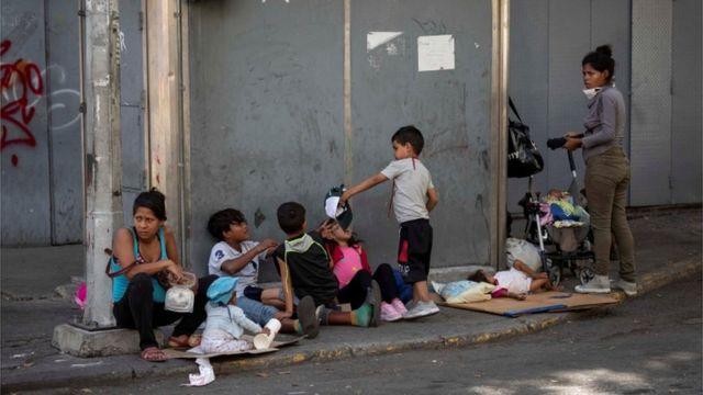 Una familia pide limosna en las calles de Caracas.