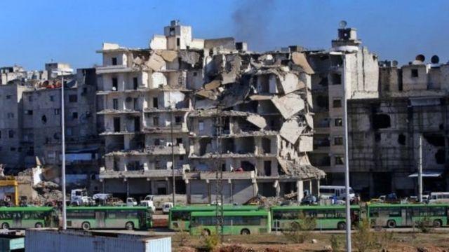 حافلات تستخدم في عمليات الإجلاء تقف وسط الدمار في شرق حلب