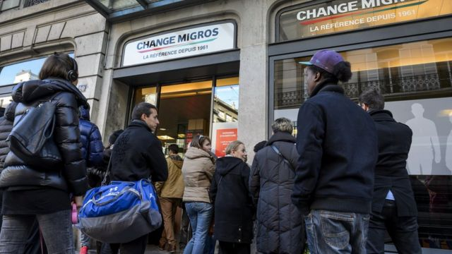 People queue at a bureau de change in Geneve