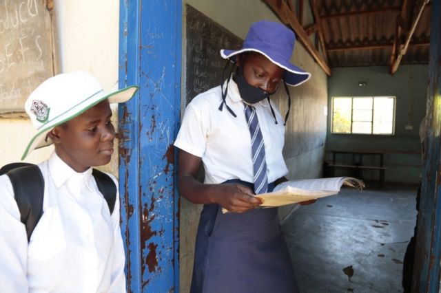 تلميذتان في إحدى المدارس في زيمبابوي تنظران إلى كتاب معاً
