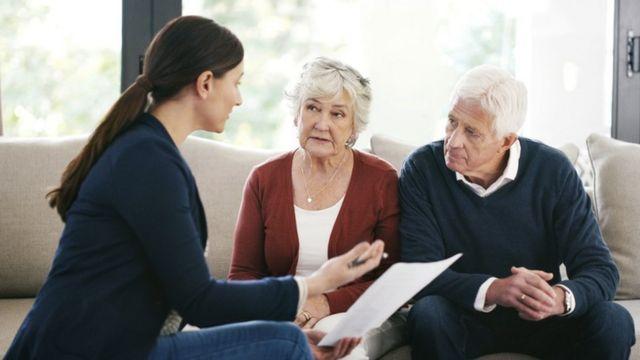 Mulher segura um papel e conversa com dois idosos