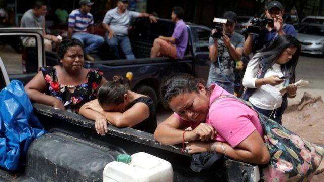 یک زن در بیرون پزشکی قانونی منتظر است تا جسد عضو خانوادهاش که در زندان کشته شده را ببیند