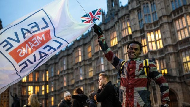 ブレグジット協定の採決が行われた英議会前で「離脱とは離脱のこと」と旗を振るブレグジット支持者(15日、ロンドン)