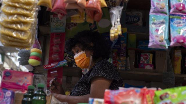 Una mujer atiende en un comercio en El Salvador.